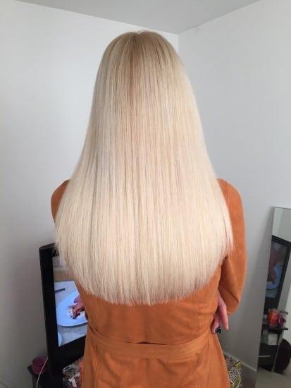Long platinum blonde hair on lady wearing orange jacket