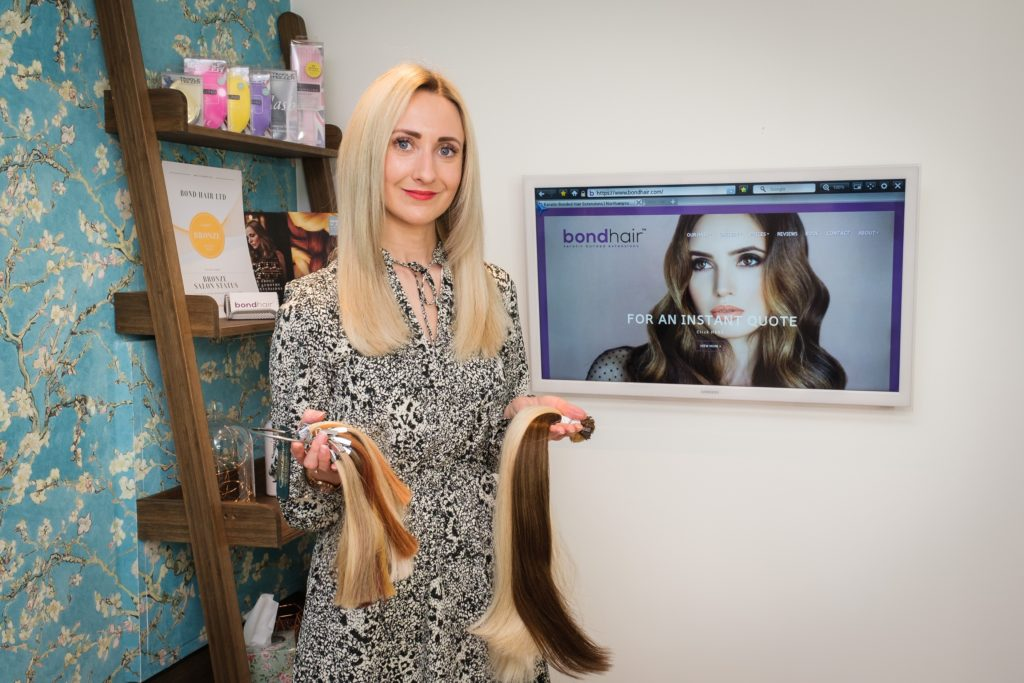 Faye Perkins owner of bond hair extensions holding hair in home salon