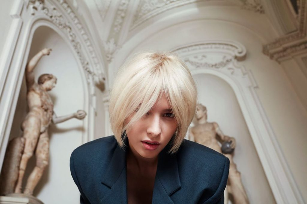 Lady wearing blue blazer with platinum blonde bob looking into camera