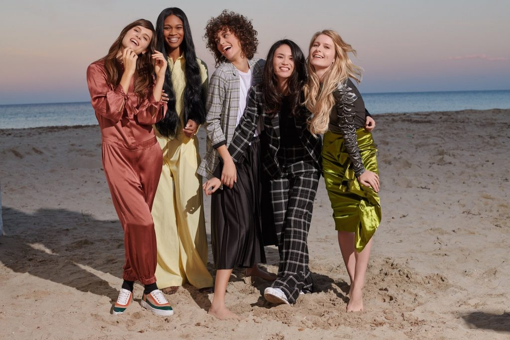 Five ladies in fashionable clothes smiling on a beach