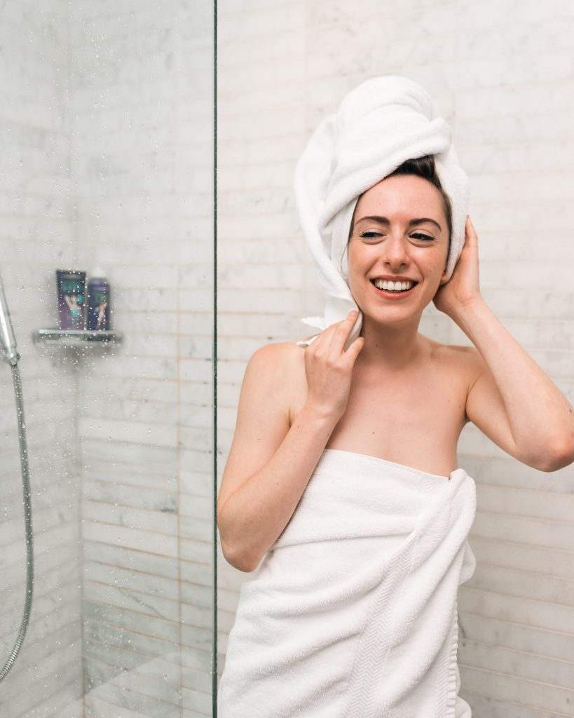 Woman getting out of shower wearing white towel with towel on head