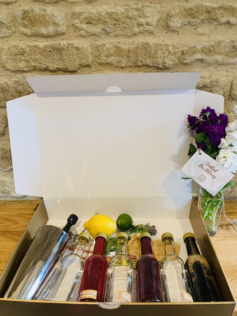 Open box with cocktail ingredients and equipment